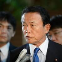 Taro Aso, deputy prime minister and finance minister, speaks to the media at the prime minister's residence in Tokyo on Tuesday. | BLOOMBERG