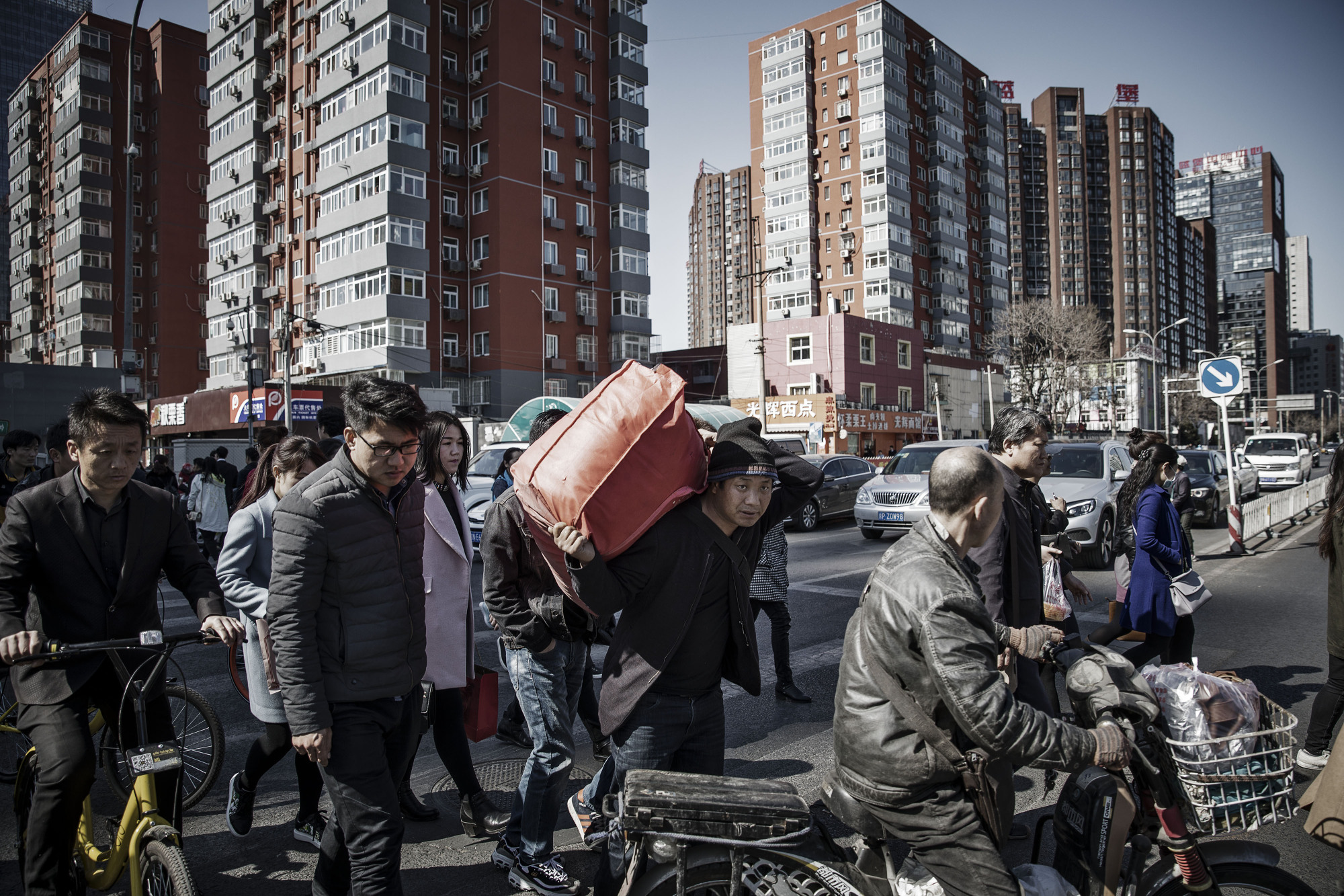People cross a street in Beijing. China is thinking about how to avoid what happened in Japan after its epic bust in the 1990s and the decades of stagnation that followed. | BLOOMBERG
