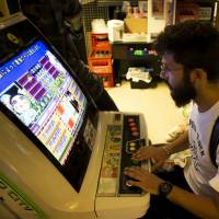 Tourists play on arcade video game machines inside the Super Potato video game store in Akihabara, Tokyo, on Aug. 8.   BLOOMBERG