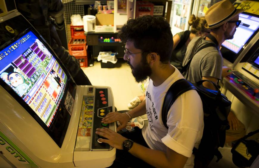 Tourists play on arcade video game machines inside the Super Potato video game store in Akihabara, Tokyo, on Aug. 8.
