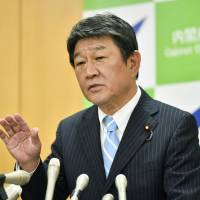 Economic revitalization minister Toshimitsu Motegi speaks at a news conference Monday as Japan's economy marked the longest growth run since 2006 in the April-June period. | KYODO