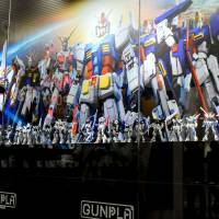 A woman shoots video during a media preview of Gundam Base Tokyo on Thursday in Tokyo's Odaiba waterfront district. | SATOKO KAWASAKI