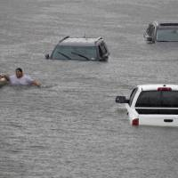 Jesus Rodriguez rescues Gloria Garcia after rain from Hurricane Harvey flooded Pearland, in the outskirts of Houston, Sunday. | REUTERS