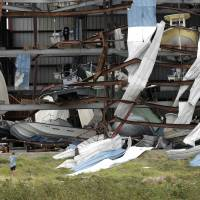 A group checks damage to a boat storage facility caused by the effects of Hurricane Harvey in Rockport, Texas, on Sunday. | AP