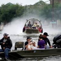 People are rescued from flood waters from Hurricane Harvey on an air boat in Dickinson, Texas, Sunday. | REUTERS