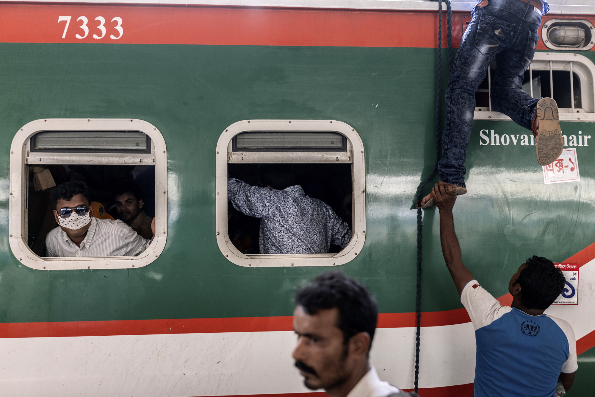 A man climbs onto the roof of a train at a station in Bangladesh. Kawasaki Heavy Industries Ltd. and Mitsubishi Corp. have won a ¥40 billion order to supply 144 train cars and maintenance depot equipment for Bangladesh's first rapid transit railway system. | BLOOMBERG