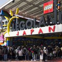 Visitors wait in long lines to enter the Legoland Japan theme park in Nagoya in March, before its grand opening on April 1. Four months later, the outdoor theme park is seeking to address criticism that its ticket prices are too expensive. | BLOOMBERG