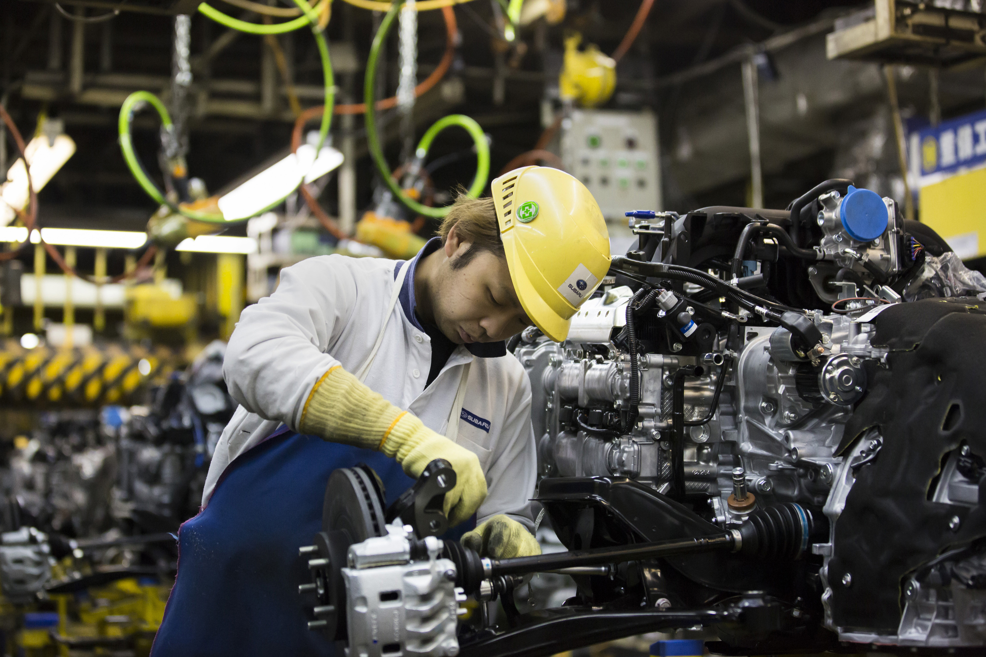 A worker assembles an engine on a production line in Ota, Gunma Prefecture, in March 2017. Japan saw core private-sector machinery orders fall in June for the third straight month. | BLOOMBERG