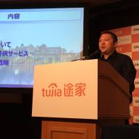 Yang Changle, chief operating officer of Chinese home-sharing giant Tujia, announces a plan to expand its business in Japan by partnering with Rakuten Inc. at a news conference in Tokyo on Wednesday. | ALEX K.T. MARTIN