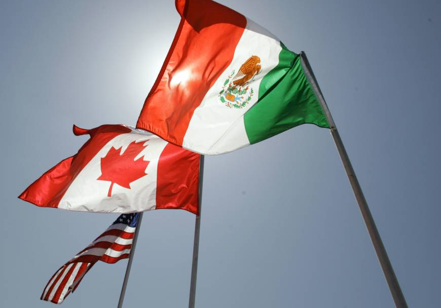 National flags representing the United States, Canada, and Mexico fly in the breeze as leaders of the North American Free Trade Agreement meet in New Orleans in 2008. Renegotiations of the three-way trade pact are set to start Wednesday in Washington D.C. | AP