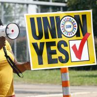 A United Auto Workers supporter uses a bullhorn to remind workers to vote while standing outside an employee vehicle entrance at the Nissan vehicle assembly plant in Canton, Mississippi, on Friday. | AP