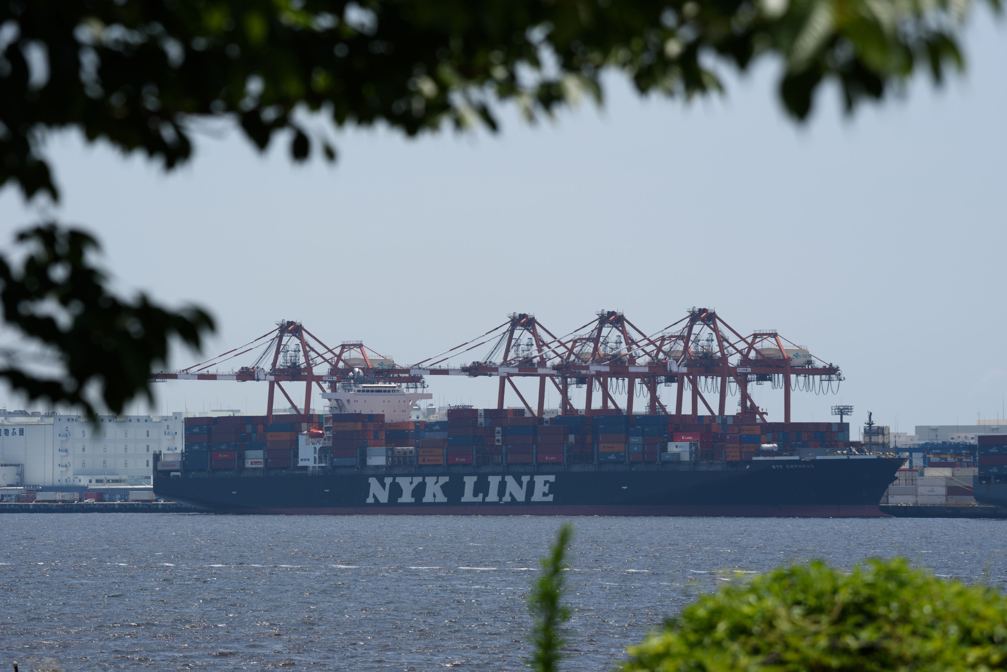 A Nippon Yusen KK container ship sits berthed at a shipping terminal in Tokyo in July. The largest container line in Japan plans to test a remote-controlled vessel in 2019. | BLOOMBERG