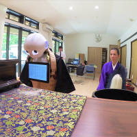 Pepper, the robot created by SoftBank Robotics, bows during a Buddhist ritual with a monk at a temple in Yokohama on July 20. Nissei Eco Co. has programmed Pepper to recite sutras as part of its expanded funeral service business. | COURTESY OF NISSEI ECO CO.