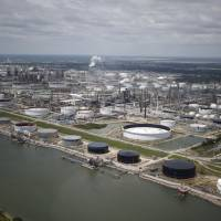 Oil refinery storage tanks stand in this aerial photograph taken above Texas City, Texas, Wednesday. Unprecedented flooding from the Category 4 storm that slammed into the state's coast last week, sending gasoline prices surging as oil refineries shut, may also set a record for rainfall in the contiguous U.S., the weather service said Tuesday. | BLOOMBERG