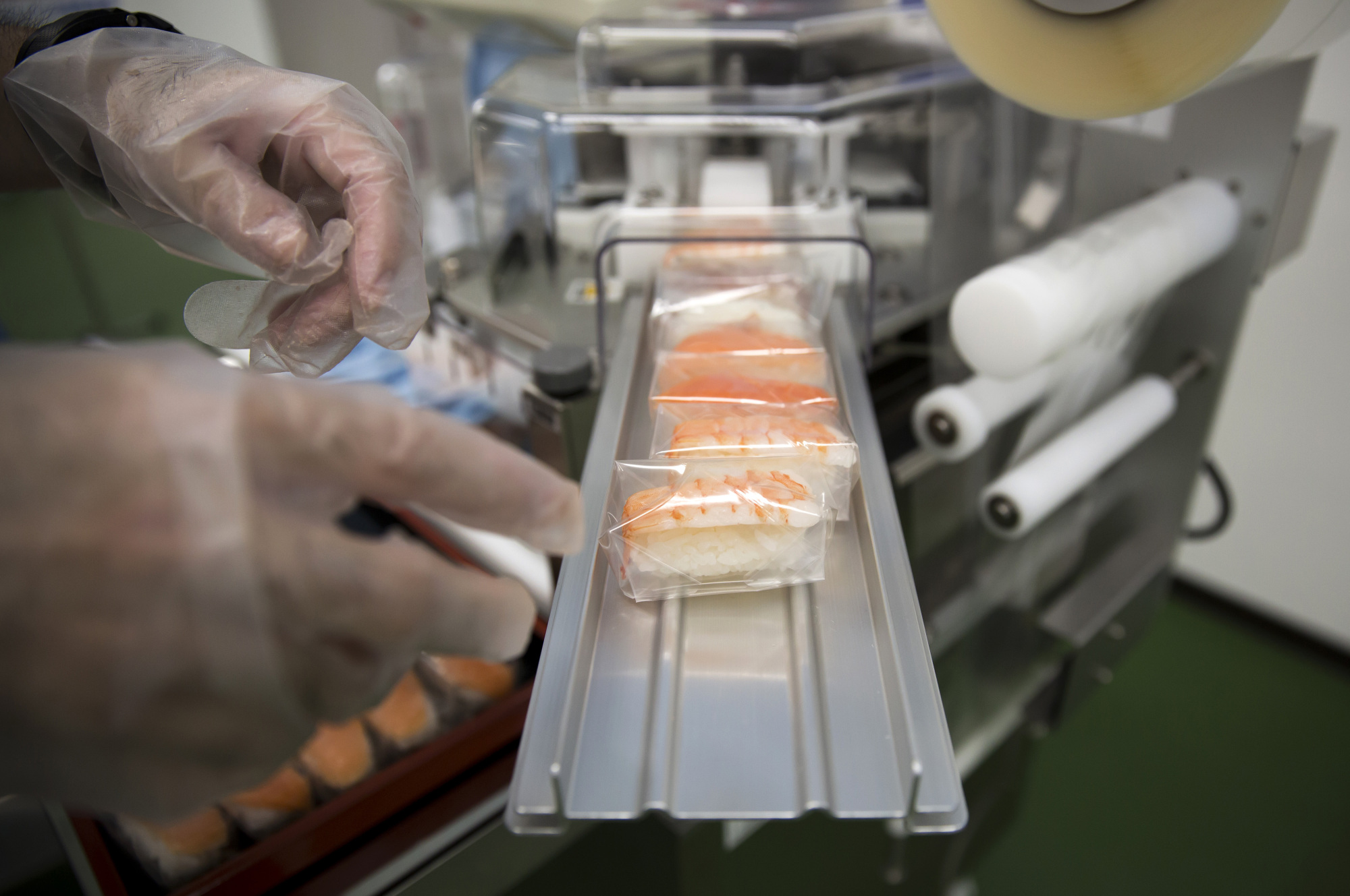 Wrapped pieces of sushi exit a Suzumo Machinery Co. machine during a demonstration at its factory in Kawashima, Saitama Prefecture, on Aug. 7. Suzumo Machinery's robots are used by about 70,000 customers around the world, ranging from sushi chains to factories, and account for about 70 percent of the market for the equipment at restaurants, according to Suzumo's estimates. | BLOOMBERG