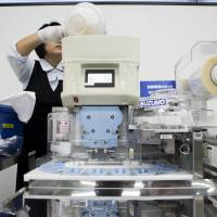 An employee puts a bowl of rice into a Suzumo Machinery Co. sushi machine during a demonstration. | BLOOMBERG