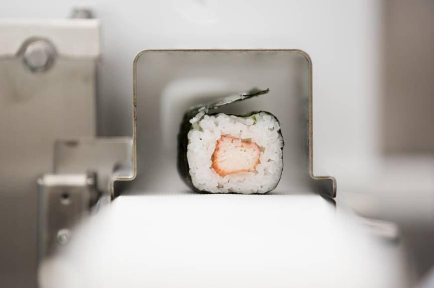 A roll of maki-sushi exits a Suzumo Machinery Co. sushi machine during a demonstration at the company