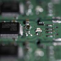 Apple Inc. joins a Bain Capital-led consortium's last-minute bid for Toshiba Corp.'s chip unit. | BLOOMBERG
