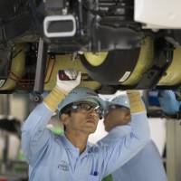 Toyota Motor Corp. employees work on an assembly line at its plant in Toyota, Aichi Prefecture. | BLOOMBERG