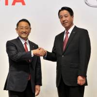 Toyota Motor Corp. President Akio Toyoda (left) and Mazda Motor Corp. head Masamichi Kogai attend a news conference in Tokyo on Friday evening to announce a capital tie-up aimed at the joint development of electric vehicles. | YOSHIAKI MIURA