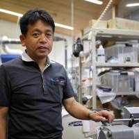 Kyoto University professor Hiroaki Yano, who is leading research into using wood pulp fibers to make lighter auto parts, is seen in his laboratory in Kyoto on July 25. | REUTERS