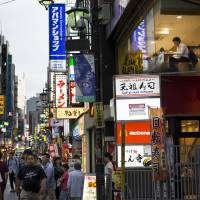 Store signs are displayed on a street near Kichijoji Station in Tokyo on Aug. 23. | BLOOMBERG