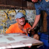 A police officer tries to comfort a man by giving him a glass of water after his brother was killed in a spate of drug-related violence Wednesday night. | REUTERS