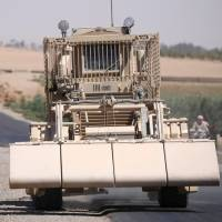A U.S. military de-mining vehicle leads a convoy on the main road in Raqqa, Syria, on Monday. | REUTERS
