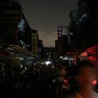 People walk on a street during a massive power outage in Taipei on Aug. 15. | REUTERS