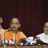 Indian Health Minister J.P. Nadda (right) looks on as Uttar Pradesh state Chief Minister Yogi Adityanath addresses a news  conference after visiting the Baba Raghav Das Medical College Hospital in Gorakhpur, India, on Sunday. | AP