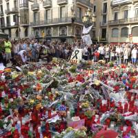 People stand next to flowers, candles and other items set up on the Las Ramblas boulevard in Barcelona as they pay tribute Sunday to the victims of the Barcelona attack, three days after a van plowed into the crowd, killing 13 people and injuring over 100. | AFP-JIJI
