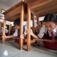 Pupils protect themselves under a table during a tsunami drill at Tanjung Benoa school in Badung, Indonesia's Bali resort island, Tuesday. | ANTARA FOTO / NYOMAN BUDHIANA / VIA REUTERS