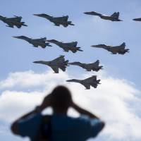 A man watches Russian military jets performing in Alabino, outside Moscow, on Aug. 12. The Russian military says major war games, the Zapad (West) 2017 maneuvers, set for next month will not threaten anyone. | AP