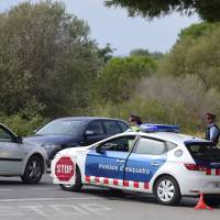 Police officers block a road near Alcanar, Spain, Sunday as part of an operation to find a suspect of Barcelona's attack. Police said they had cast a dragnet for 22-year-old Younes Abouyaaqoub, who media reports say was the driver of a van that smashed into people on Barcelona's busy Las Ramblas boulevard on Thursday, killing 13. | AFP-JIJI