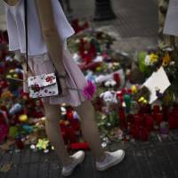 A girl stands next to candles and flowers placed on the ground for the victims after an attack that left many killed and wounded in Barcelona, Spain, Wednesday. Police in northeastern Spain said Wednesday they have found a belt charged with real explosives in a house used by the Barcelona attacks extremist cell. | AP