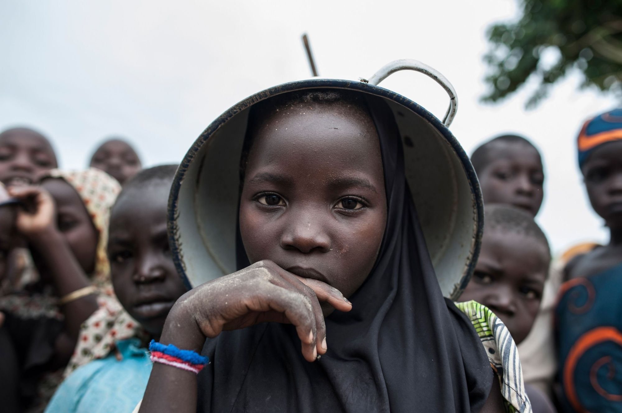 A girl using a pot as a hat poses with other children on Tuesday at a camp for internally displaced people in Gwoza, northeastern Nigeria. Boko Haram seized Gwoza in July 2014. It was retaken by Nigerian troops in March 2015, but extremists continued to raid nearby villages.   AFP-JIJI