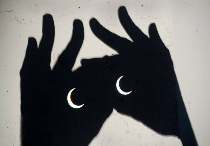 An annular eclipse is seen through binoculars on May 20, 2012, in Sacramento, California. | AP