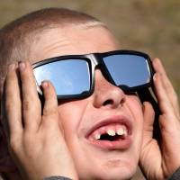 Cooper Jackson tries out his new solar glasses in a designated eclipse viewing area in a campground near Guernsey, Wyoming, Sunday. | REUTERS