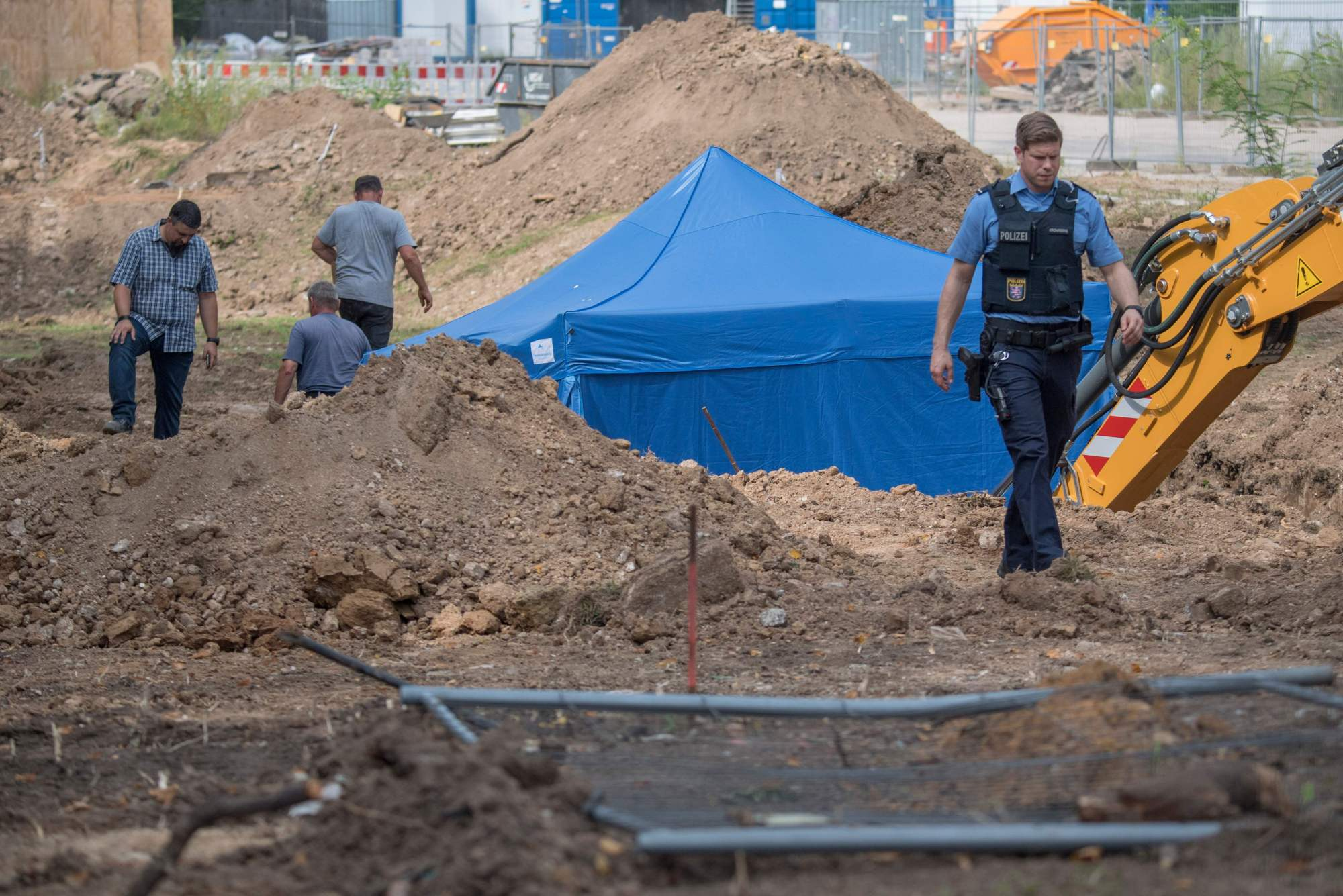 A policeman walks past a blue tent covering a British World War II bomb that was found during construction work on Wednesday in Frankfurt am Main, western Germany. The disposal of the bomb that is planned for Sunday requires the evacuation of around 70,000 people. | BORIS ROESSLER / DPA / VIA AFP-JIJI