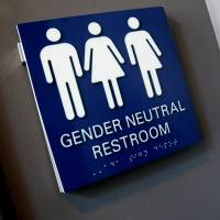A gender-neutral sign stands outside a restroom during the 15th annual Philadelphia Trans-Health Conference on June 9, 2016.   REUTERS