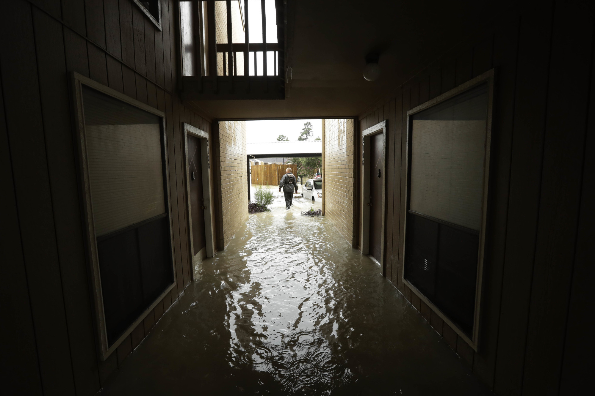 A man searches for people to help in an apartment complex as floodwaters from Tropical Storm Harvey rose Tuesday in Kingwood, Texas. | AP