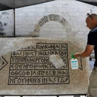 A conservationist works on a 1500-year-old mosaic floor bearing Greek writing, discovered near Damascus Gate in Jerusalem's Old City, as it is displayed at the Rockefeller Museum in Jerusalem on Wednesday.   REUTERS
