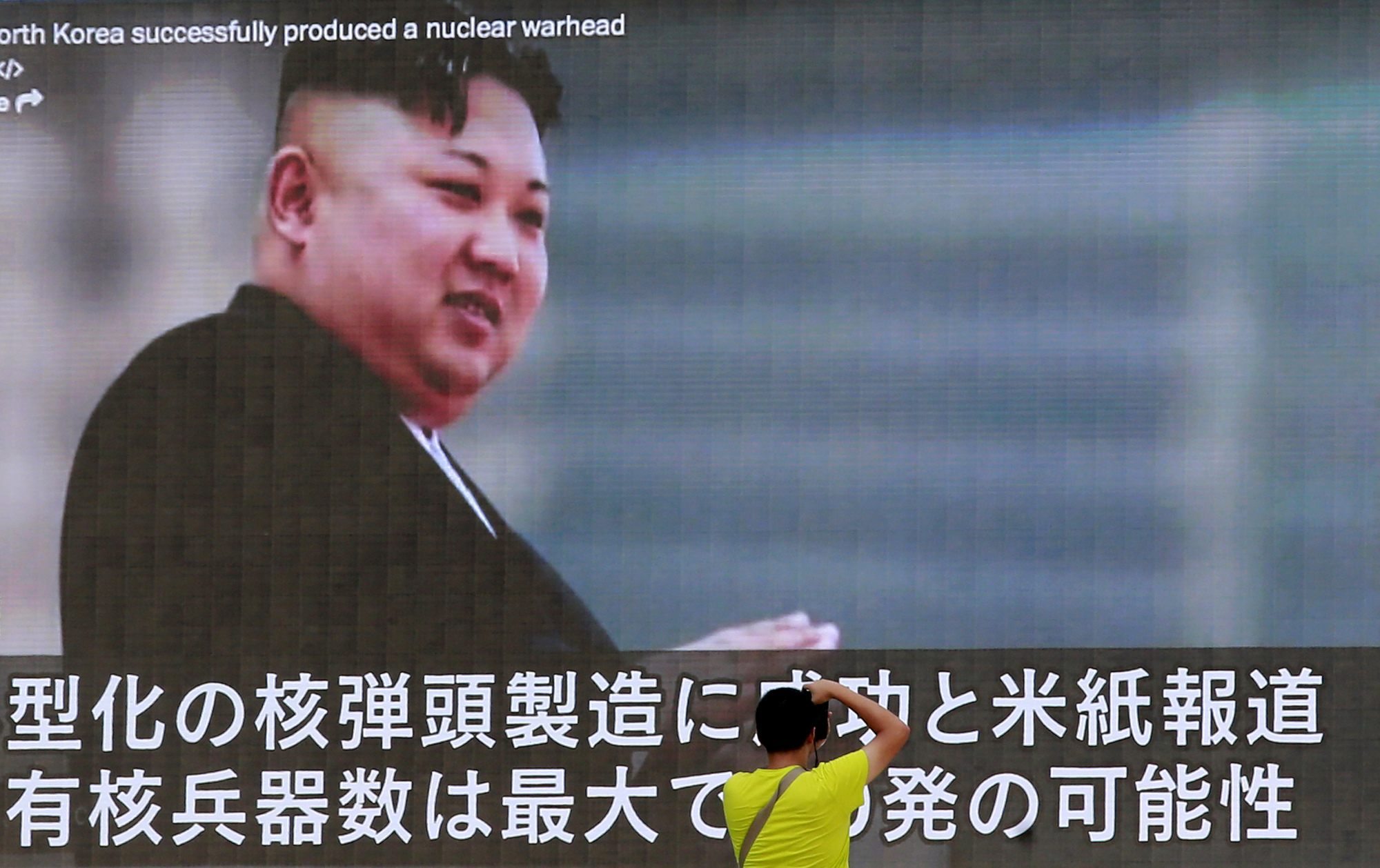 A man takes a photo of a TV news program in Tokyo showing an image of North Korean leader Kim Jong Un Wednesday. In an exchange of threats, U.S. President Donald Trump warned Pyongyang of 'fire and fury like the world has never seen' and the North's military claimed Wednesday it was examining plans for attacking Guam. | AP