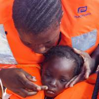 Sara Traore, a 2-year old girl from Cote d'Ivoire, is rescued from a rubber boat sailing out of control about 15 miles north of Al Khums. Libya, on Tuesday. | AP