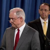 Deputy Attorney General Rod Rosenstein watches (at right) as Attorney General Jeff Sessions steps away from the podium during a news conference at the Justice Department in Washington Friday on leaks of classified material threatening national security. | AP