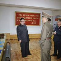 North Korean leader Kim Jong Un visits the Chemical Material Institute of the Academy of Defense Science in this photo released Wednesday. Posters for two apparently new missiles, the Pukguksong-3 (right) and an unknown Hwasong model are displayed on the walls. | AP
