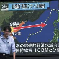 A man in Tokyo on Saturday passes a public TV broadcast of news of North Korea's test-firing of its second intercontinental ballistic missile.   AP
