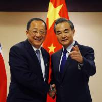 North Korean Foreign Minister Ri Yong Ho (left) is greeted by his Chinese counterpart, Wang Yi, prior to their bilateral meeting in the sidelines of a regional foreign ministers' meeting Sunday in Manila. | AP