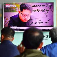 People watch a television news report at a railway station in Seoul last September showing file footage of North Korean leader Kim Jong Un. | AFP-JIJI