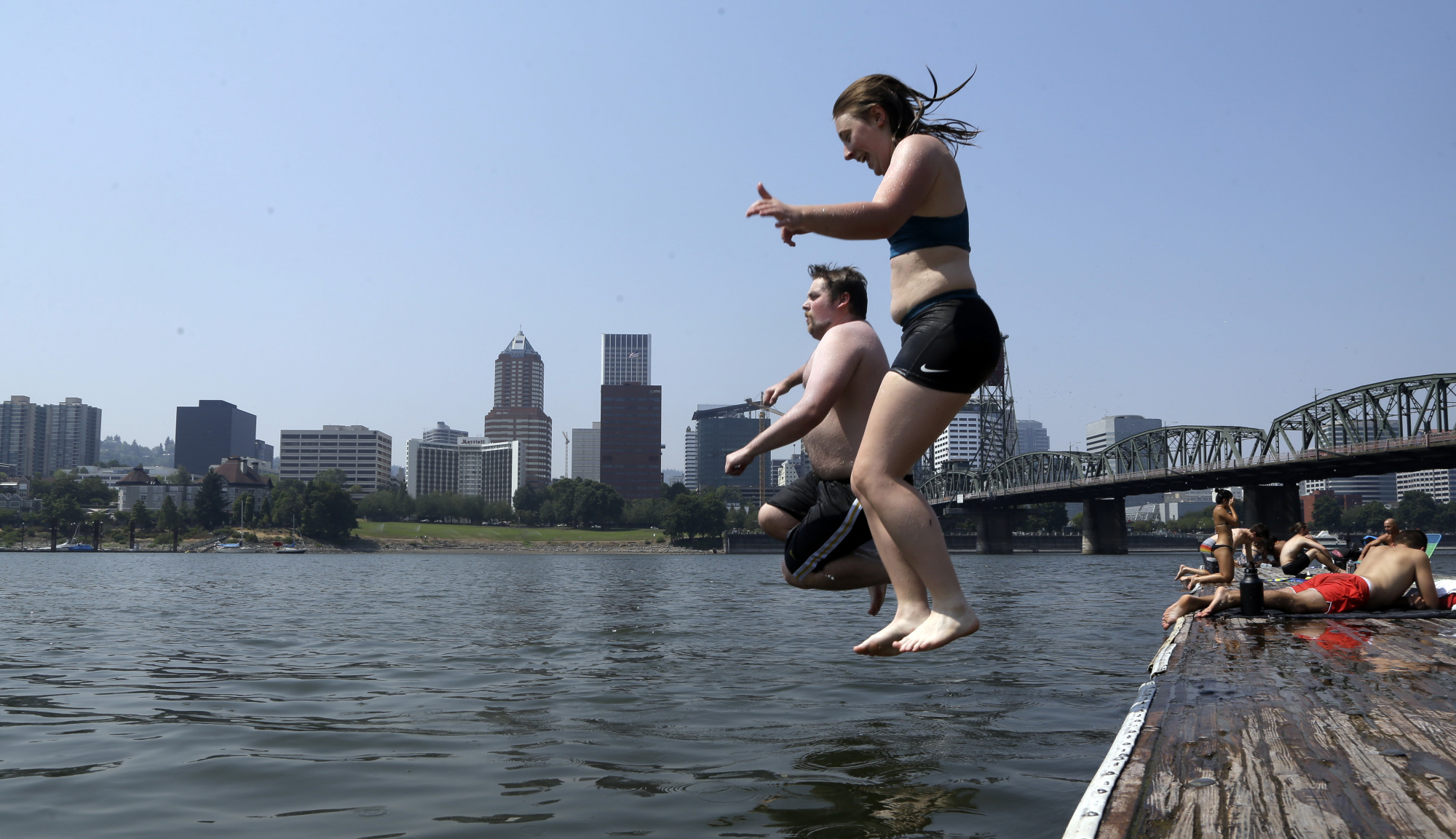 Residents of Portland, Oregon, leap into the Willamette River on Wednesday. | AP